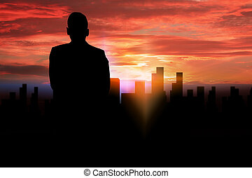 silhouette businessman standing looking to the city.