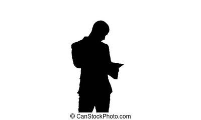 Silhouette Busy man talking on mobile phone and holding tablet PC