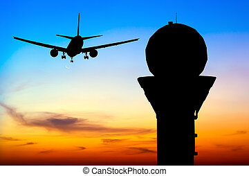 Silhouette commercial airplane take off over airport control tower at sunset