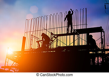 silhouette Construction workers work in preparation for binding rebar and concrete work. and the environment around the work site. over Blurred construction worker on construction site