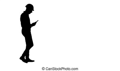 Silhouette Contractor engineer inspecting construction site holding digital tablet