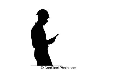 Silhouette Contractor engineer in hardhat inspecting construction site holding digital tablet
