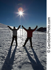 Silhouette couple raising hands with ski poles on snow...