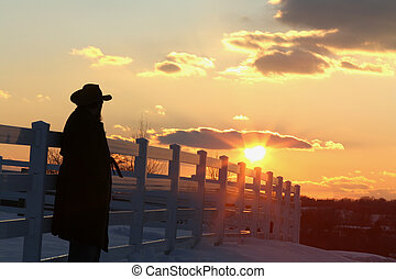 silhouette of a man in a cowboy hat leaning against a fence looking out at the sunset