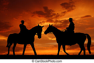 Silhouette cowboys with horses