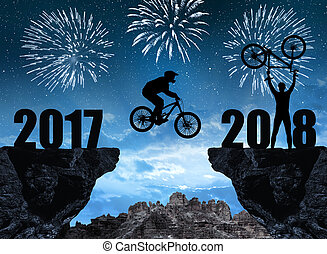 Silhouette cyclist jumping into the New Year 2018, in the...