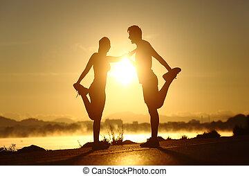 silhouette, de, a, fitness, couple, étirage, à, coucher soleil