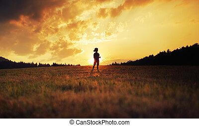 silhouette, de, heureux, gosse, jouer, sur, pré, à, coucher soleil
