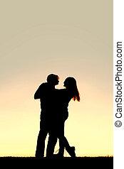 silhouette, de, heureux, jeune danser couples, à, coucher soleil