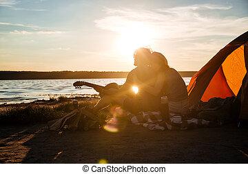 silhouette, di, coppia, seduta, appresso, turistico, tenda, e, abbracciare