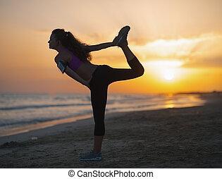 silhouette, di, idoneità, giovane, stiramento, su, spiaggia, a, crepuscolo