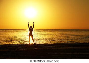 silhouette, di, il, donna, con, il, mani elevate, contro, uno, fondo, di, uno, alba, su, il, mare, coast.