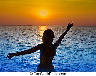 silhouette, di, il, donna, dare, mani, a, uno, tramonto, in, il, mare