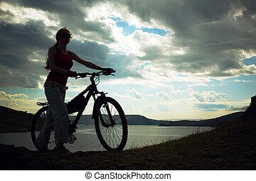 silhouette, di, il, ragazza, con, uno, bicicletta, contro, montagne