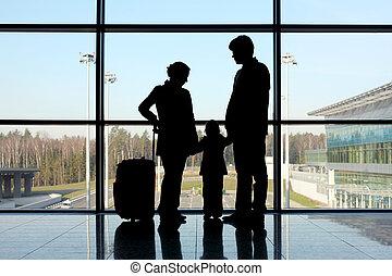 silhouette, di, madre, padre figlia, con, bagaglio, standing, appresso, finestra, in, aeroporto