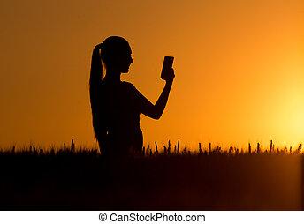 silhouette, di, ragazza, presa, selfie