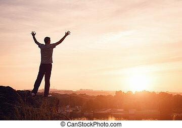 silhouette, di, uno, uomo, con, raised-up, braccia, a, il, tramonto