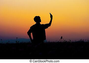 silhouette, di, uomo, selfie., silhouette, di, uomo, proposta, a, cielo tramonto, fondo.