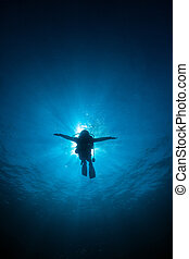 Silhouette diver sunrays behind at Underwater blue background in sea, Thailand