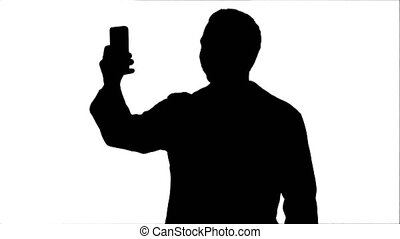 Silhouette Doctor or medic taking a selfie with front camera of smartphone track matte
