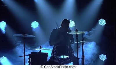 Silhouette drummer playing on drum kit on stage in a dark studio with smoke and neon lighting. Dynamic neon lighting effects. Performance vocal and musical band. Close-up