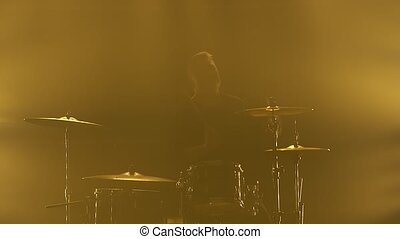 Silhouette drummer playing on drum kit on stage in a dark studio with smoke and neon lighting. Performance vocal and musical band. Close-up