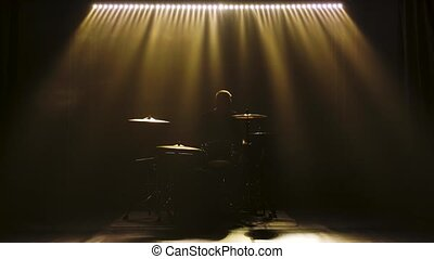 Silhouette drummer playing on drum kit on stage in a dark studio with smoke and neon lighting. Dynamic neon lighting effects. Performance vocal and musical band. Slow motion