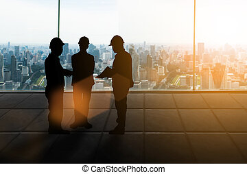 Silhouette engineer Good deal.three engineer business people shaking hands over blurred city background sunset pastel. heavy industry and safety at work concept