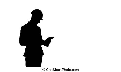 Silhouette Engineer in safety helmet conducting inspection with tablet