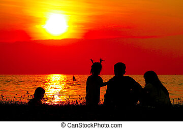 silhouette family on beach blurred sunset sky