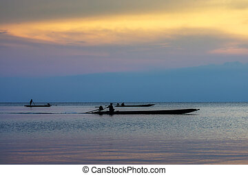 silhouette fishermans on the lake with twilight sky.