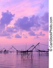 Silhouette fishing net trap at sunrise seascape