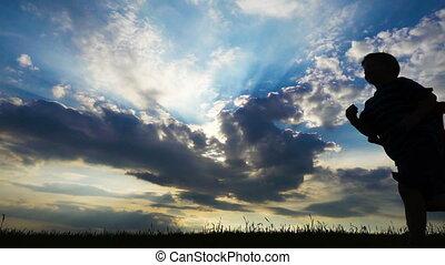 silhouette, garçons, deux, contre, champ, courant, coucher soleil