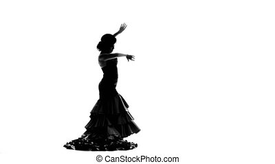 Woman in a long dress with a magnificent tail dancing flamenco gracefully moving her hands. White background. Silhouette