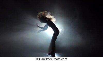 Silhouette girl dancing in smoky studio twerk dance. Slow motion