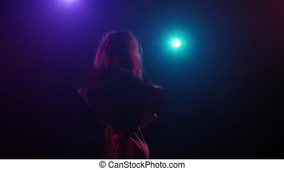 Silhouette girl in rhythmic dancing against disco lights. Close-up