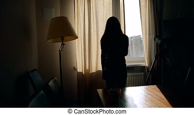 Silhouette girl looks out the window with a cup of tea