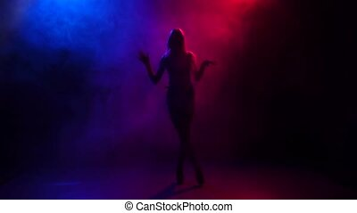 Silhouette girl pj is dancing in color smoke, slow motion