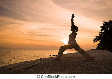 silhouette girl posing yoga on beautiful beach during sunset