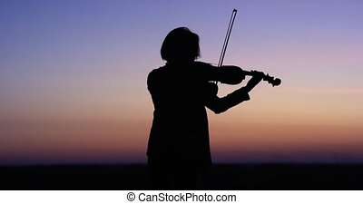 Silhouette girl violinist playing the violin at sunset sky background. Slow motion 4k.