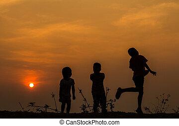 silhouette, groep, van, vrolijke , kinderen spelende, op, weide, ondergaande zon , s
