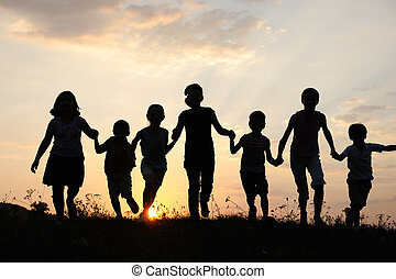 Silhouette, group of happy children playing on meadow,...