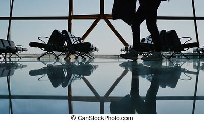 Silhouette group of passenger walking with luggage at airport.