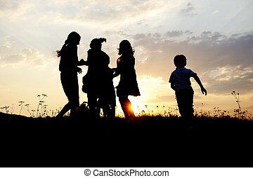 silhouette, groupe, de, heureux, enfants jouer, sur, pré, coucher soleil, été