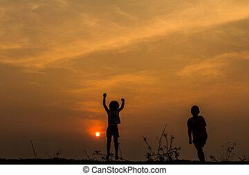 silhouette, groupe, de, heureux, enfants jouer, sur, pré, coucher soleil, s