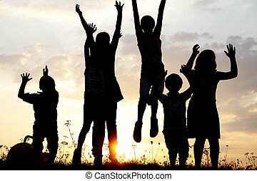 silhouette, gruppe, von, glücklich, kinder, spielen, auf, wiese, sonnenuntergang, sommerzeit