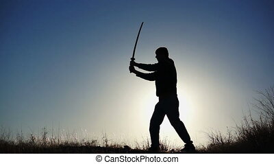 Silhouette of a male figure practicing using the martial arts sword.