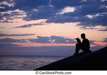 Silhouette guy sitting on breakwater in evening near sea,...