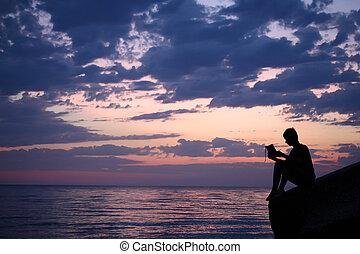 Silhouette guy sitting on breakwater in evening near sea, reads book