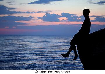 Silhouette guy sitting on breakwater in evening near sea